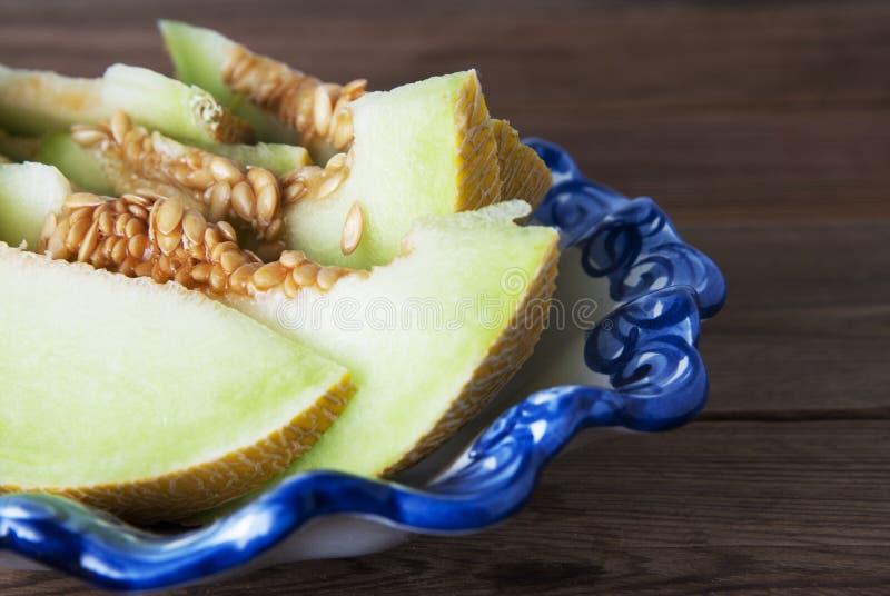Kantaloep gele verse die meloen met gesneden meloen wordt geïsoleerd, in mooie uitstekende blauwe plaat, houten lijstachtergrond  stock foto's