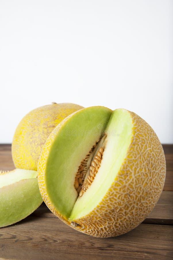 Kantaloep gele verse meloen met gesneden meloen, houten lijst, grijze achtergrond De zomervruchten De ruimte van het exemplaar stock afbeeldingen