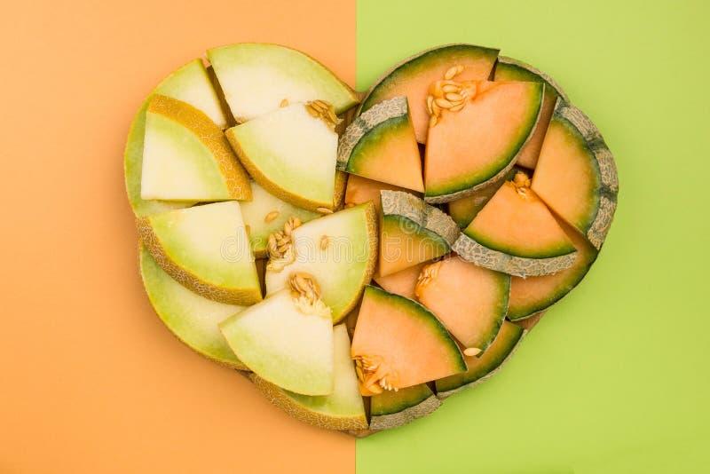 Kantalupen-und Blatthonig-Melonen-Scheiben in der Herz-Form, Diät-Konzept stockfotos
