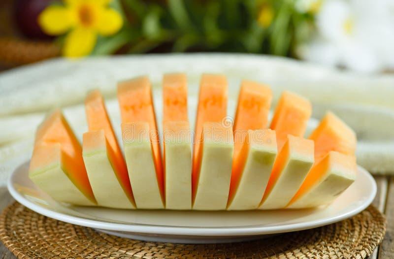 Kantalupenmelone geschnitten auf weißer Platte stockbild