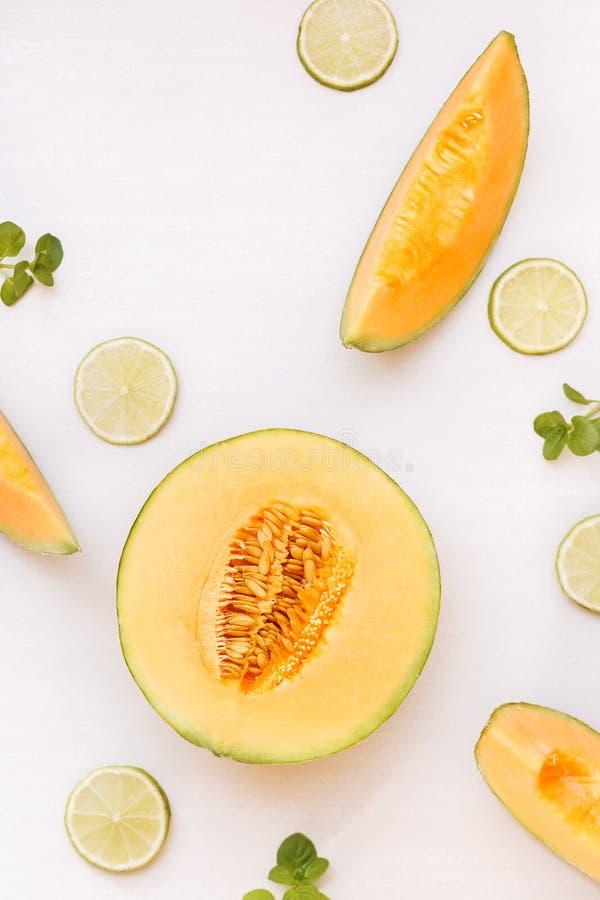 Kantalupenmelonenhälfte und Scheiben und Kalk stockfoto