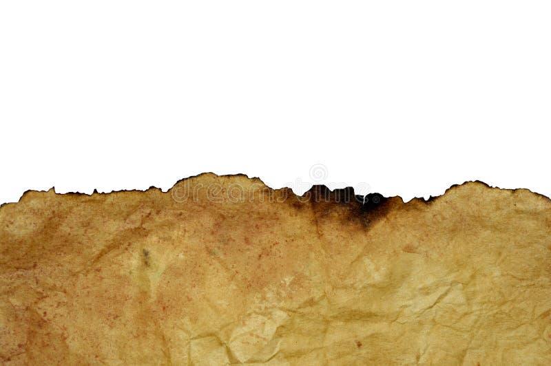 Kanten av det utbrända arket av gammalt gulnat rufsat till pergament arkivbilder