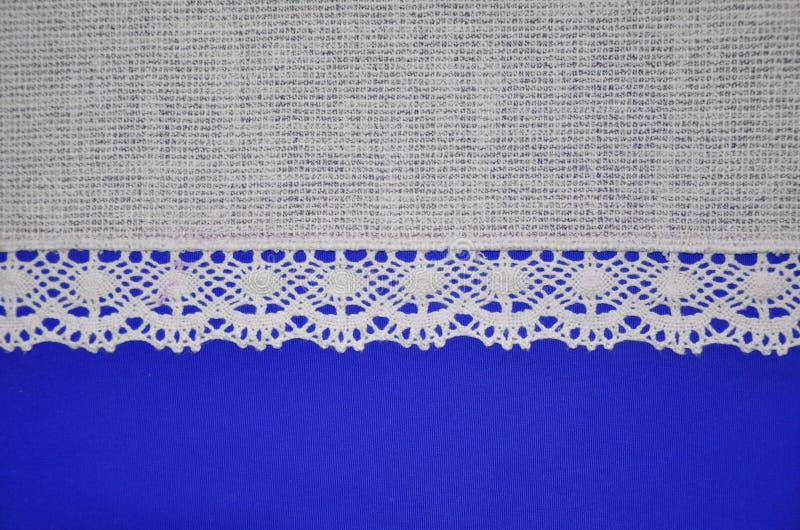 Kanten uitstekende lint textiel en blauwe achtergrond stock fotografie