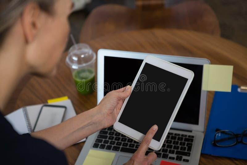 Kantjusterad bild av affärskvinnan som använder minnestavlan royaltyfria bilder