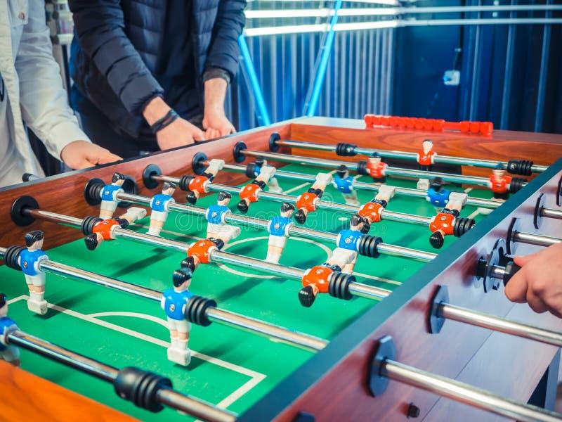Kantjusterad bild av aktivt folk som spelar foosball tabellfotbollplaers Vänner spelar tillsammans tabellfotboll royaltyfri foto