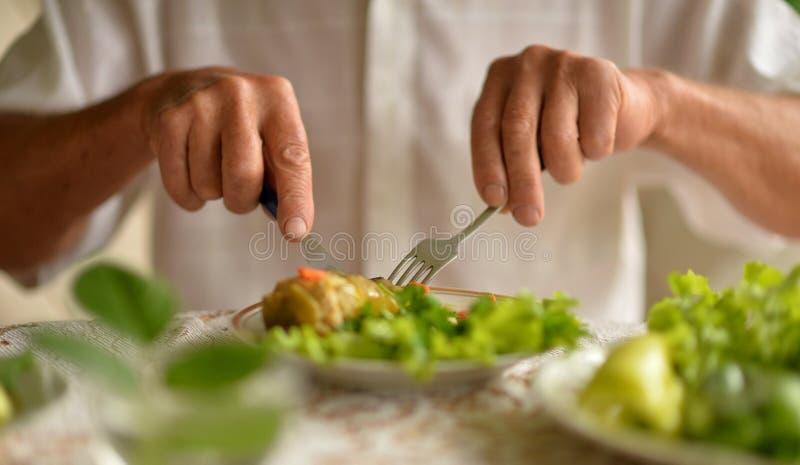 Kantjusterad bild av att äta för hög man royaltyfri foto