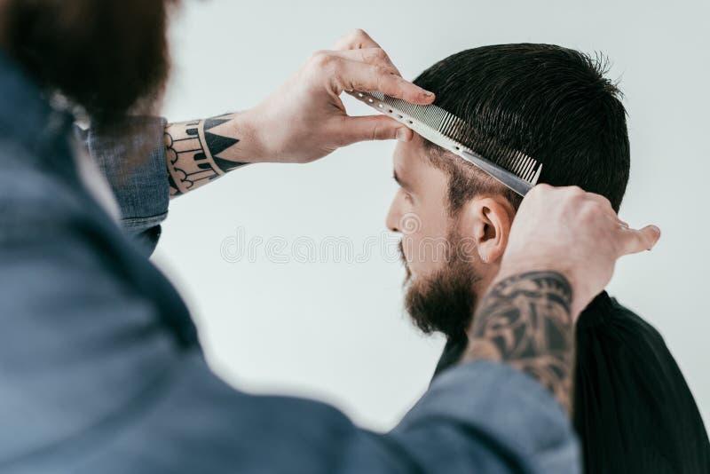 kantjusterad bild av barberaren som klipper klienthår med sax och hårkammen på frisersalongen royaltyfria bilder