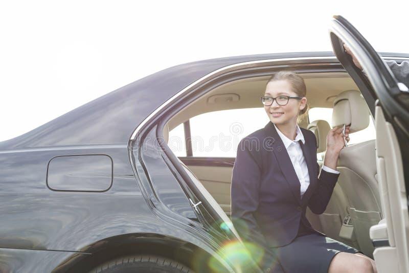 Kantjusterad bild av dörren för affärsmaninnehavbil för kollega mot himmel arkivfoton