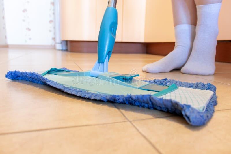 Kantjusterad bild av den härliga unga kvinnan som använder en blå golvmopp, medan göra ren golvet i kök royaltyfria bilder