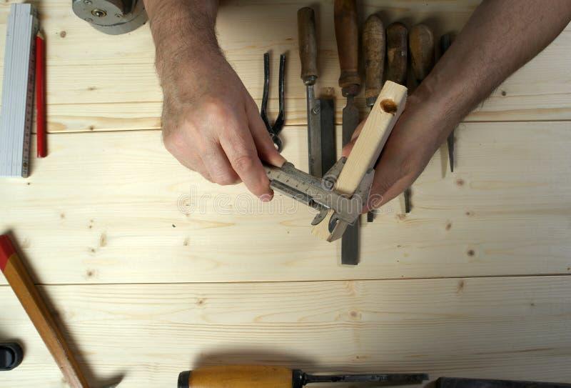 Kantjusterad bild av den höga snickaren som mäter trä i seminarium arkivfoton