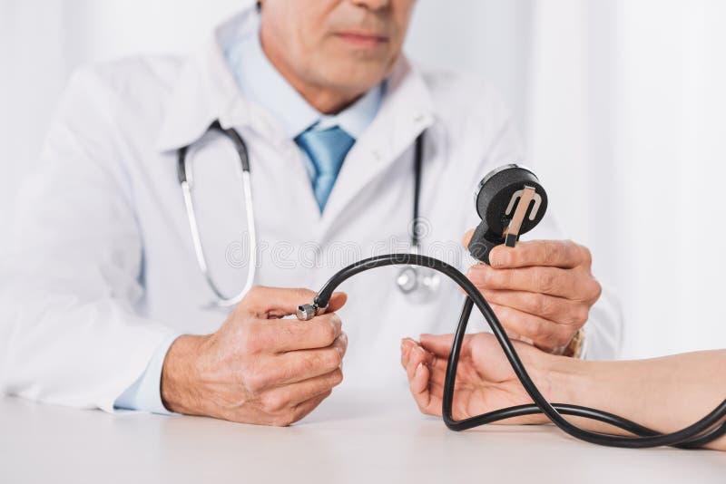kantjusterad bild av den manliga doktorn som mäter den kvinnliga patienten arkivbilder