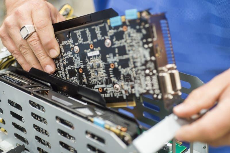 Kantjusterad bild av den manliga teknikern som reparerar videokortet i fabriks- bransch för dator arkivfoto