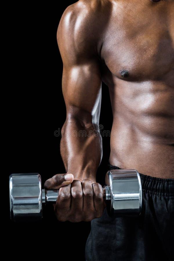 Kantjusterad bild av den muskulösa mannen som övar med hanteln arkivbilder