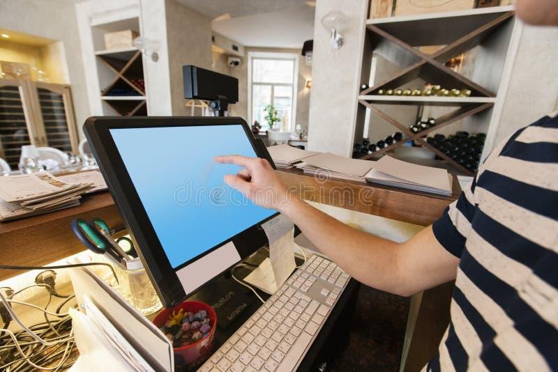 Kantjusterad bild av den rörande datorskärmen för kassörska på restaurangräknaren arkivfoton