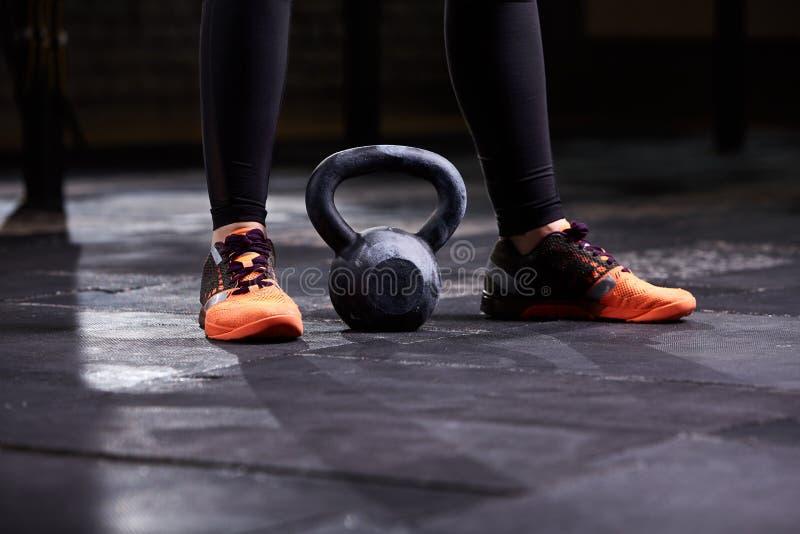 Kantjusterad bild av den unga kvinnan, ben i den svarta damasker, orange gymnastikskor och kettlebell Crossfit genomkörare arkivfoton