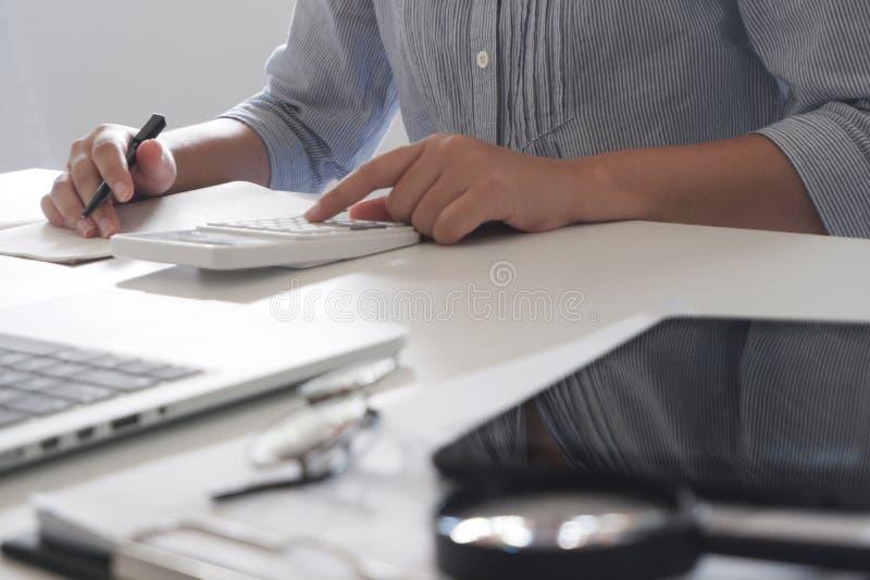Kantjusterad bild av den yrkesmässiga affärskvinnan som arbetar på hennes kontor via den unga kvinnliga chefen för bärbar dator s arkivfoto