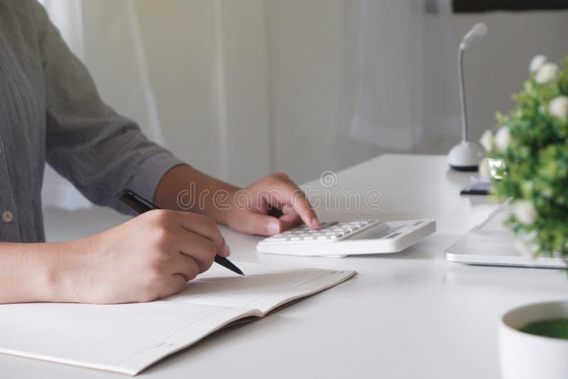 Kantjusterad bild av den yrkesmässiga affärskvinnan som arbetar på hennes kontor via den unga kvinnliga chefen för bärbar dator s royaltyfri bild