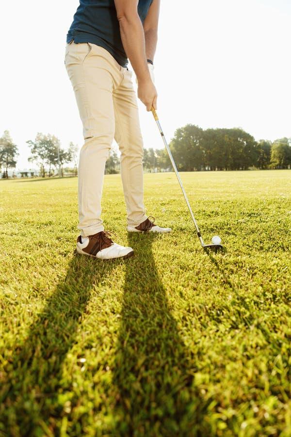 Kantjusterad bild av en golfare som sätter golfboll på gräsplan royaltyfri bild