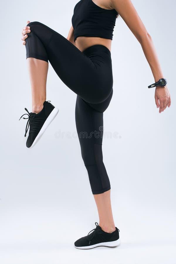 Kantjusterad bild av en idrottskvinna som sträcker benet, medan stå över grå bakgrund fotografering för bildbyråer