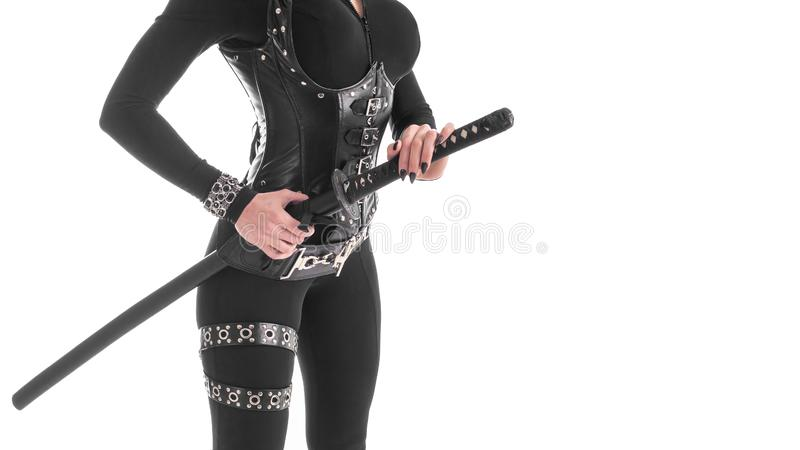 Kantjusterad bild av en kvinna i den svarta cosplay dräkten som tar bort katanasvärdet från skidan Isolerat på vit arkivbild
