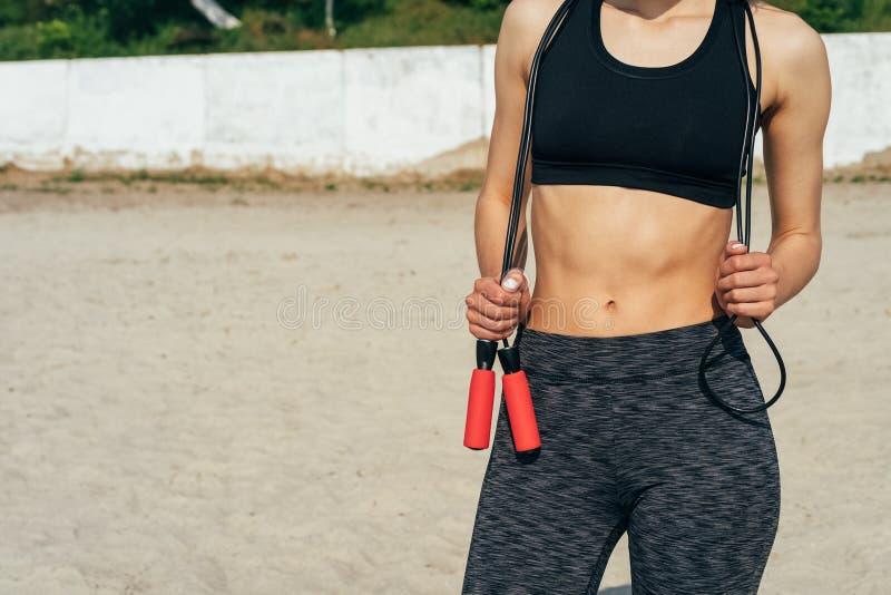 Kantjusterad bild av en spenslig kvinna i sportswear med ett hoppande over r fotografering för bildbyråer