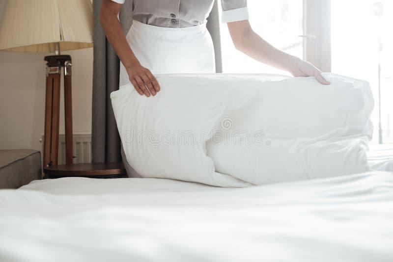 Kantjusterad bild av en städerskadanandesäng i hotellrum royaltyfri fotografi