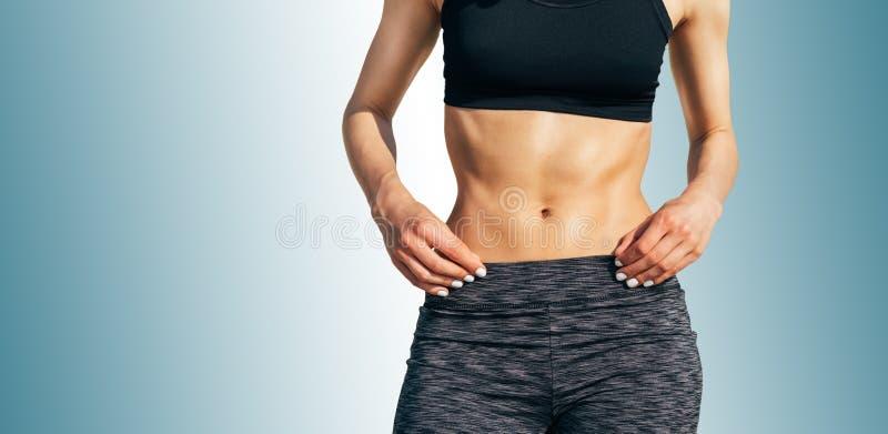 Kantjusterad bild av en ung sportig kvinna med en muskulös buk arkivfoton