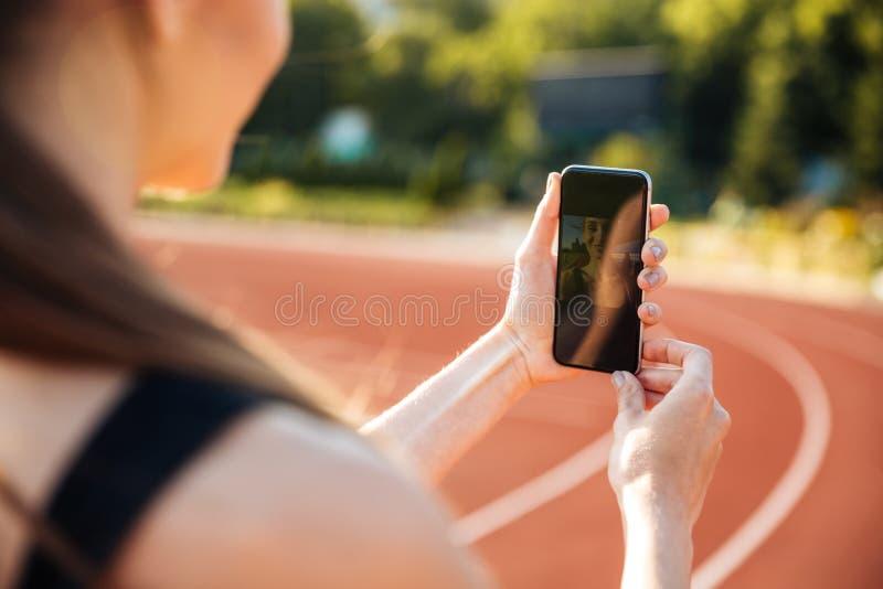Kantjusterad bild av fotoet för idrottskvinnadanandeselfie på mobiltelefonen royaltyfria foton