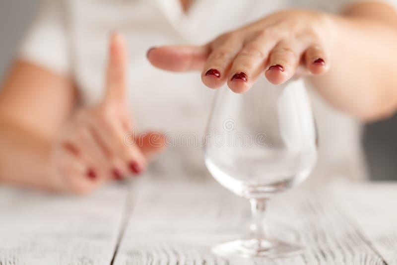 Kantjusterad bild av gesten och att vägra för kvinnavisningstopp till drinen royaltyfria foton