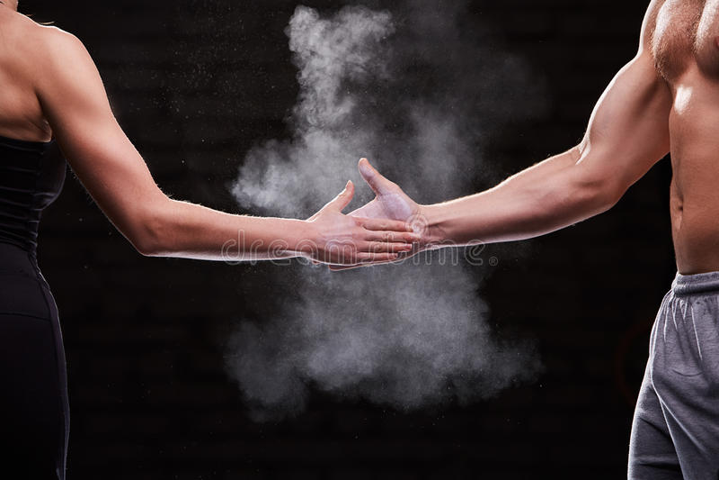 Kantjusterad bild av händer av mannen och kvinnan för idrottsman nen den muskulösa mot mörk bakgrund royaltyfri foto