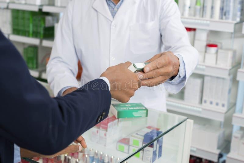 Kantjusterad bild av kunden för kemistGiving Medicine To kvinnlig royaltyfri fotografi