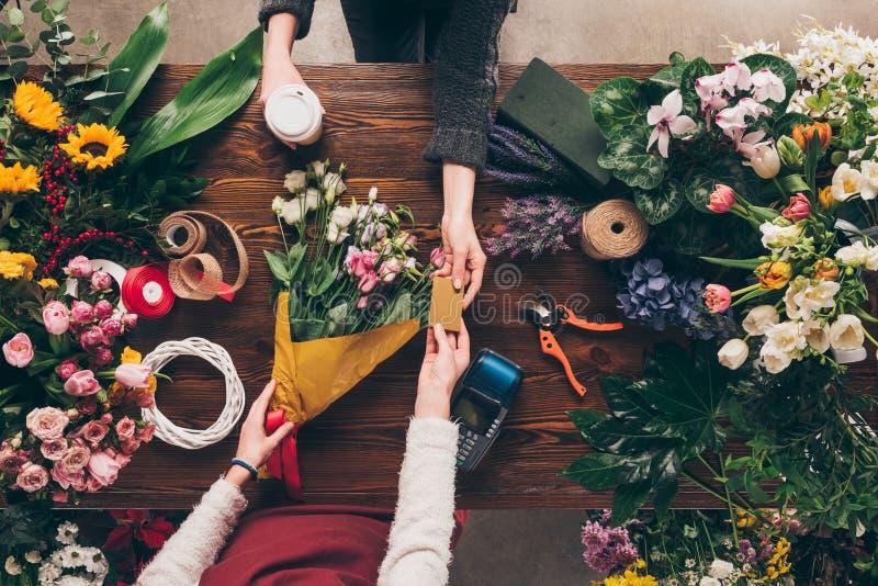 kantjusterad bild av kunden som ger blomsterhandlarekreditkorten till lön royaltyfri fotografi