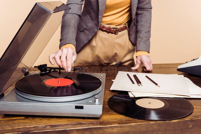 kantjusterad bild av kvinnan som är roterande på vinyl arkivfoto