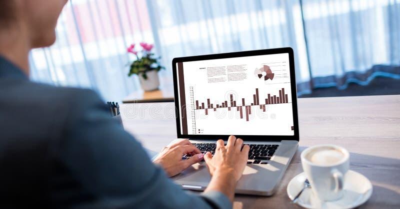 Kantjusterad bild av kvinnan som i regeringsställning förbereder grafer på bärbara datorn arkivbilder
