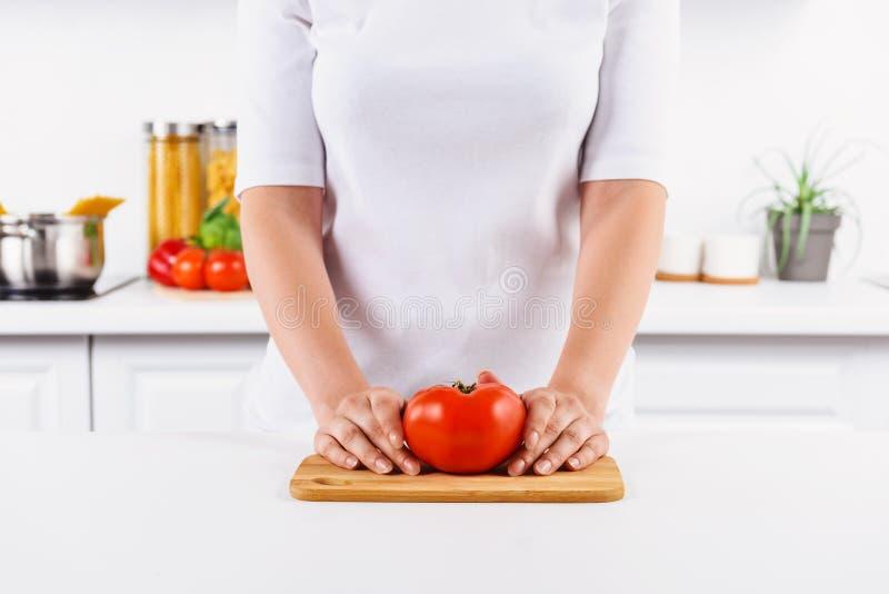 kantjusterad bild av kvinnan som rymmer den mogna tomaten på skärbräda fotografering för bildbyråer