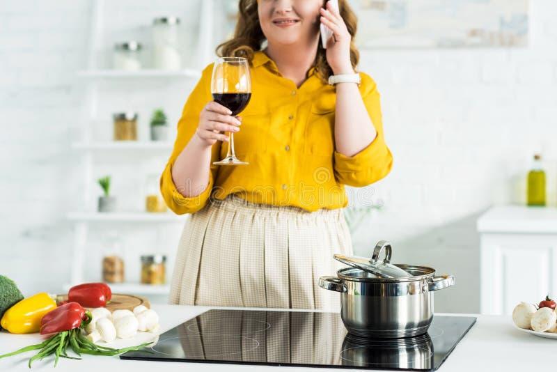 kantjusterad bild av kvinnan som talar vid smartphonen och dricker vin royaltyfria foton