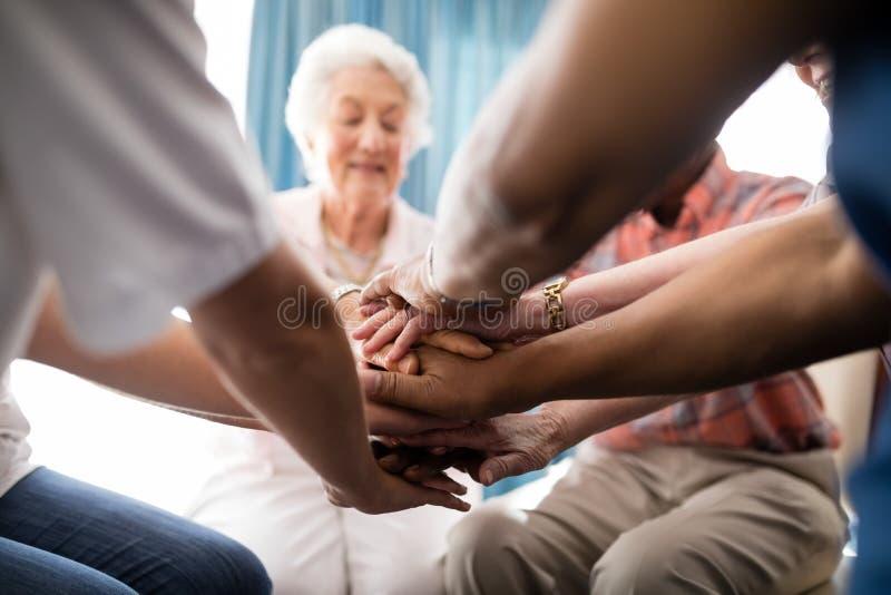 Kantjusterad bild av kvinnligt doktors- och pensionärfolk som staplar händer arkivfoto