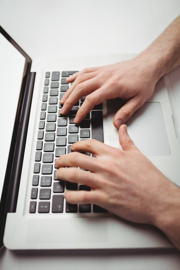 Kantjusterad bild av mannen som arbetar på bärbara datorn arkivbilder