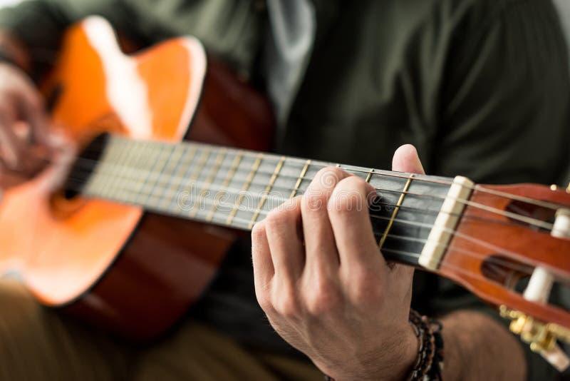 kantjusterad bild av mannen som spelar ackordet på den akustiska gitarren arkivfoton