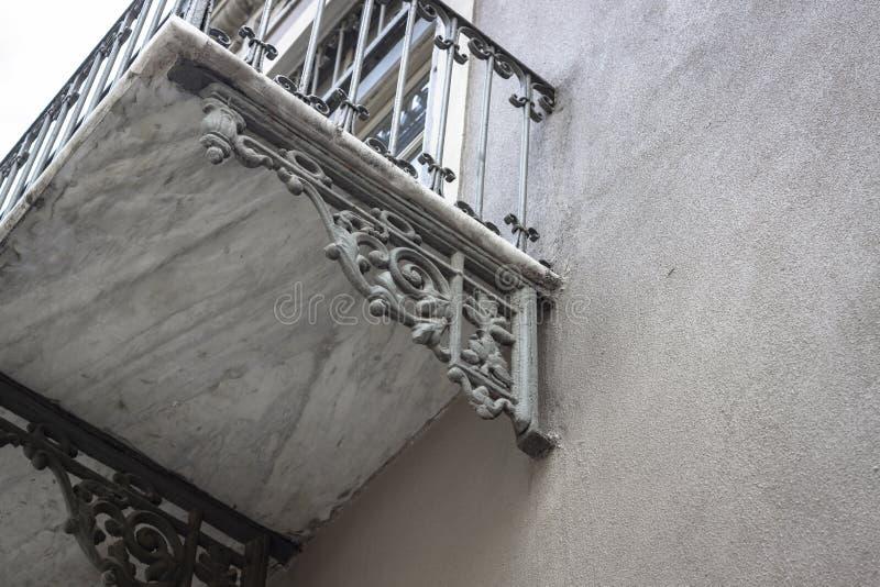 Kantjusterad fors av marmorkonsolbalkongen på den rena fasadbyggnaden royaltyfri bild