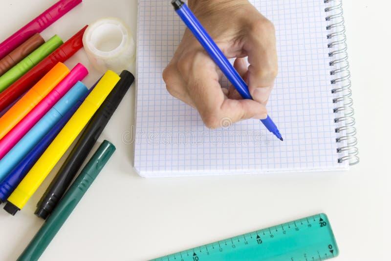 Kantjusterad handhandstil i anteckningsbok Mångfärgade markörpennor, anteckningsbok, linjal på vit Kontors- och skolateckning royaltyfri bild