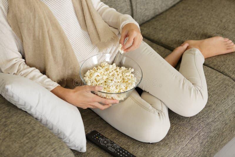 Kantjusterad kvinna på soffan som äter popcorn royaltyfri foto