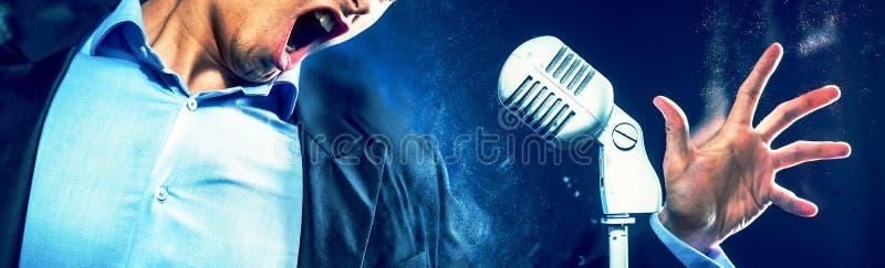 Kantjusterad mun för caucasian uttrycksfull man för bild som öppen sjunger på den vita mikrofonen för tappning r arkivfoto
