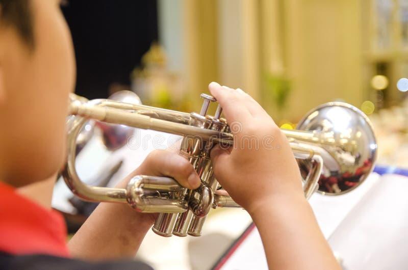 Kantjusterad och backviewbild, pojke som spelar trumpeten med en orchestr arkivfoto