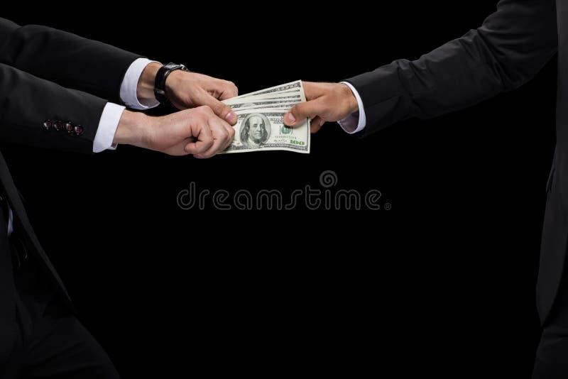 Kantjusterad sikt av affärsmannen som ger pengar och muter affärspartnern arkivfoton