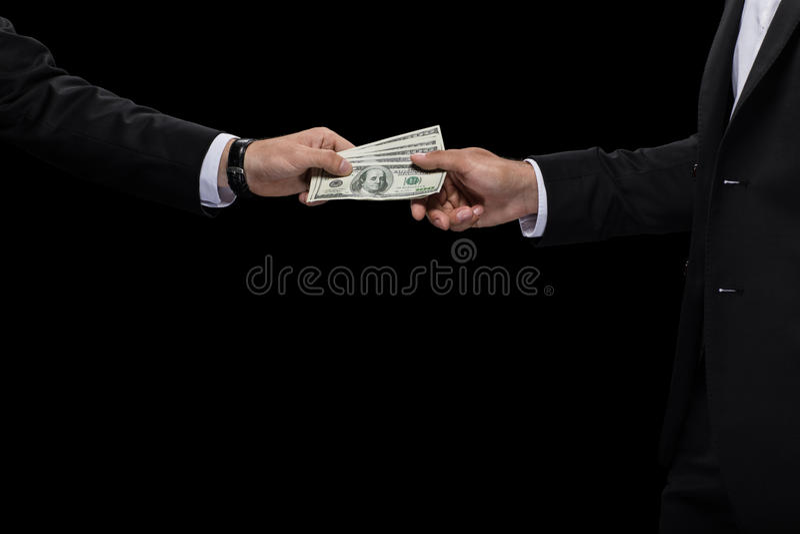 Kantjusterad sikt av affärsmannen som ger pengar och muter affärspartnern arkivbild