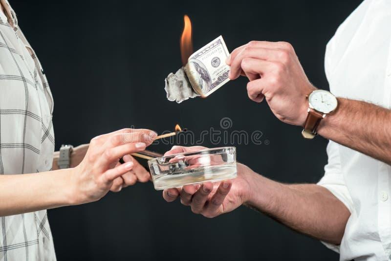 kantjusterad sikt av businesspeople som bränner dollarsedlar, royaltyfri foto