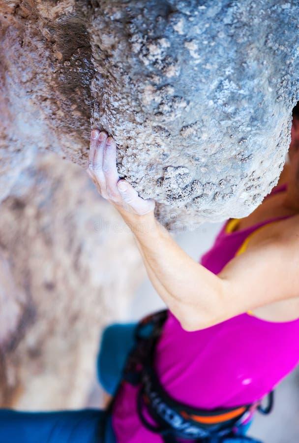 Kantjusterad sikt av den unga kvinnan som klättrar den naturliga klippan royaltyfri fotografi