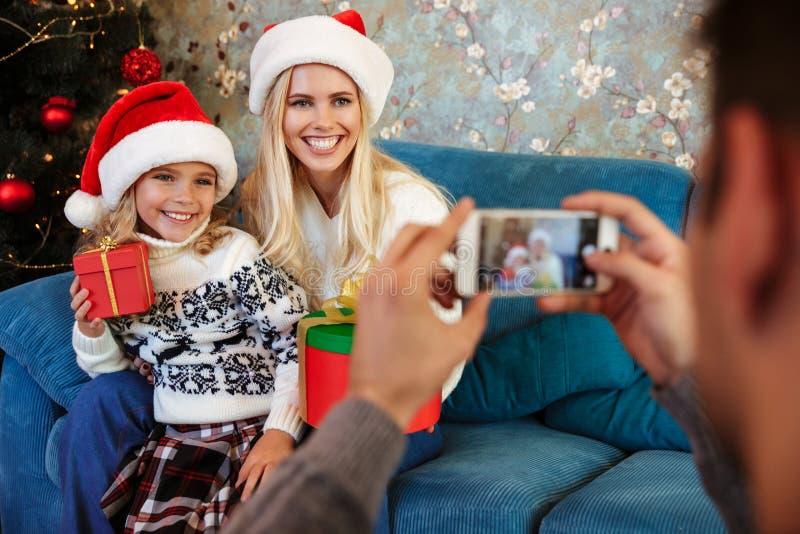 Kantjusterad sikt av fadern som tar fotoet av hans le fru och daug arkivfoton