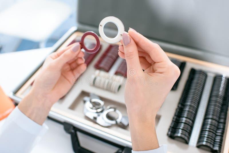 Kantjusterad sikt av hållande linser för ögonläkare royaltyfri fotografi